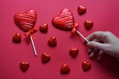 Serce kształtująca czekolada i ludzka ręka na czerwonym tle obraz royalty free