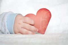 Serce kształtująca karta w dziecko ręce Zdjęcia Stock