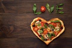 Serce kształtująca pizza dla walentynka dnia na ciemnym nieociosanym drewnianym tle z tekst miłością Zdjęcia Royalty Free