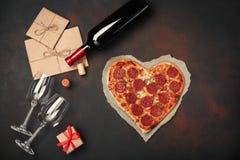 Serce kształtująca pizza z mozzarellą, sausagered, wino butelka, dwa wineglass, prezenta pudełko na ośniedziałym tle obraz stock