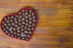 Serce kształtujący pudełko wypełniał z małymi czekolad piłkami Obraz Royalty Free
