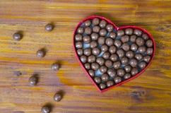 Serce kształtujący pudełko wypełniał z małymi czekolad piłkami Zdjęcia Stock