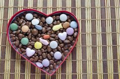 Serce kształtujący pudełko wypełniał z małymi czekolad piłkami Zdjęcie Royalty Free