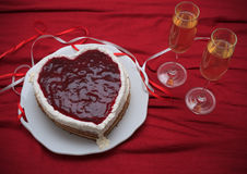 Serce kształtujący tort z czerwony marmoladowym na rocznika naczyniu i dwa szkłach szampan słuzyć na czerwonej draperii Fotografia Royalty Free