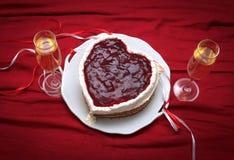 Serce kształtujący tort z czerwony marmoladowym na rocznika naczyniu i dwa szkłach szampan słuzyć na czerwonej draperii Zdjęcie Stock