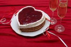 Serce kształtujący tort z czerwony marmoladowym na rocznika naczyniu i dwa szkłach szampan słuzyć na czerwonej draperii Obraz Royalty Free