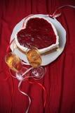 Serce kształtujący tort z czerwony marmoladowym na rocznika naczyniu i dwa szkłach szampan słuzyć na czerwonej draperii Fotografia Stock