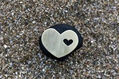 Serce na czerń kamieniu na piasku Fotografia Stock