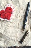 Serce na miętoszącym papierze z przestrzenią dla kopiować, obok go jest piórem Pionowo orientacja Obrazy Royalty Free