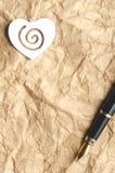 Serce na miętoszącym papierze z przestrzenią dla kopiować, obok go jest piórem Pionowo orientacja Zdjęcie Stock