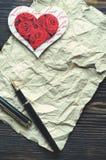 Serce na miętoszącym papierze z przestrzenią dla kopiować, obok go jest piórem Pionowo orientacja Zdjęcia Royalty Free