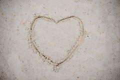 Serce, rysujący na plażowym piasku kierowy symbol na piasku myjącym Zdjęcia Royalty Free