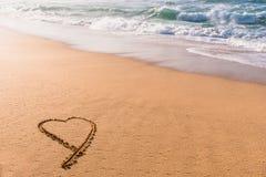 Serce rysujący w piasku na plaży przy zmierzchem zdjęcia royalty free