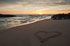 Serce rysujący w piasku na plaży przy zmierzchem Obrazy Royalty Free