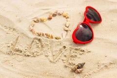 Serce skorupy i okulary przeciwsłoneczni na piasku przy plażą Zdjęcie Royalty Free