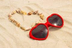 Serce skorupy i okulary przeciwsłoneczni na piasku przy plażą Obraz Stock