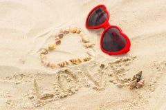 Serce skorupy i okulary przeciwsłoneczni na piasku przy plażą Obrazy Royalty Free