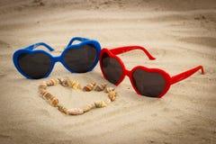 Serce skorupy i okulary przeciwsłoneczni na piasku przy plażą Obrazy Stock