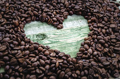 Serce w kawowych fasolach na zielonym drewno stole Fotografia Stock
