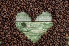 Serce w kawowych fasolach na zielonym drewno stole Odgórny widok Obrazy Stock