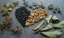 Serce wysuszone wiśnie, dokrętki i suszący liście herbata, zdjęcia stock