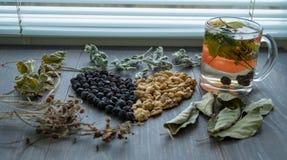 Serce wysuszone wiśnie, dokrętki i suszący liście herbata na okno, obraz stock