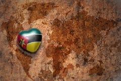 Serce z flaga państowowa Mozambique na rocznik światowej mapy pęknięcia papieru tle Fotografia Royalty Free
