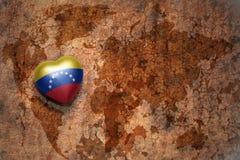 Serce z flaga państowowa Venezuela na rocznik światowej mapy pęknięcia papieru tle Zdjęcie Stock