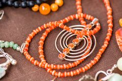 Serdolik carnelian stone necklace laying on natural brown linen tablecloth royalty free stock photo
