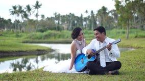 Serenadälsklingen för den unga mannen med gitarrkvinnan ser pojkvännen lager videofilmer