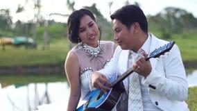Serenadälsklingen för den unga mannen med gitarrkvinnan ser pojkvännen arkivfilmer