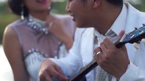 Serenadälsklingen för den unga mannen med gitarrkvinnan ser pojkvännen stock video