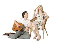 Serenade. A blond girl and a man playing guitar for her Stock Photography