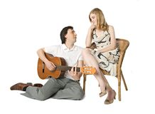 Serenade. A blond girl and a man playing guitar for her Royalty Free Stock Images