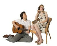 Serenade for the deaf. A woman in headphones and a man playing guitar for her Royalty Free Stock Images