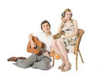 Serenade for the deaf. A woman in headphones and a man playing guitar for her Royalty Free Stock Photo