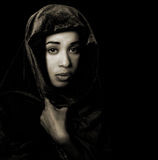 Serene African American woman wearing a shawl in monochrome. With sepia toning isolated on black Royalty Free Stock Photos