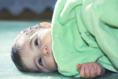Serene baby on green floor Stock Photography