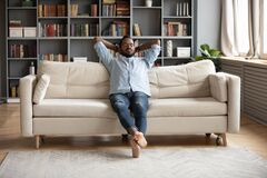 Free Serene Barefoot African Man Resting On Sofa Hands Behind Head Royalty Free Stock Image - 170451826