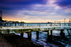 Serene Bay Sunset Environment. A serene and peaceful sunset atmosphere on a seaside with a bay on the horizon and clouds above the autumn sky Stock Photography
