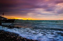 Serene Bay Sunset Environment. A serene and peaceful sunset atmosphere on a seaside with a bay on the horizon and clouds above the autumn sky Stock Image