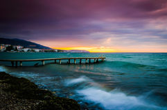 Serene Bay Sunset Environment. A serene and peaceful sunset atmosphere on a seaside with a bay on the horizon and clouds above the autumn sky Stock Photo