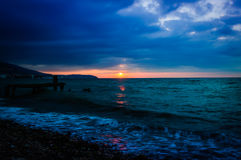 Serene Bay Sunset Environment. A serene and peaceful sunset atmosphere on a seaside with a bay on the horizon and clouds above the autumn sky Royalty Free Stock Image