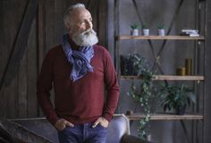 Serene beard retire male standing in apartment Royalty Free Stock Photography