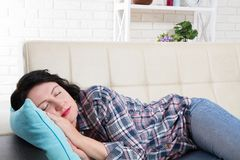 Serene Beautiful Caucasian Woman napping on the couch. After hard work royalty free stock photo