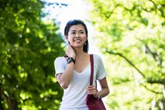 Serene young woman walking in the park. Serene beautiful young woman smiling while walking in the park in summer Stock Photography