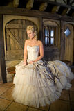 Serene beauty. Beautiful blond woman sitting in serene pose on a bench in front of a fairytale house Royalty Free Stock Photos