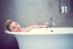 Serene blonde lying in the bath Stock Images