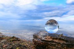 Serene blue horizon reflecting in a crystal ball. Transparent glass ball on a log reflecting calm blue water of a lake Stock Image