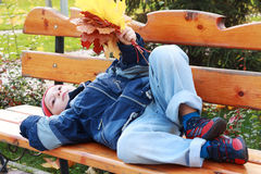 Serene boy laying on bench Stock Photos